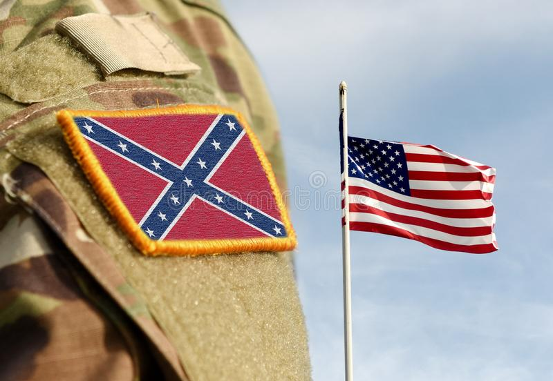 The Confederate Rebel Flag on military uniform and Flag of USA weaving in the sky. American Civil War.  stock photography