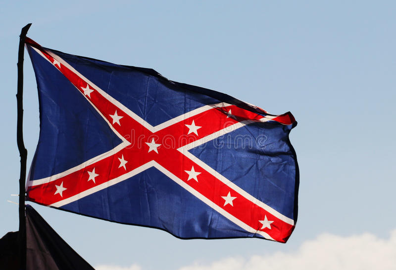 Confederate rebel flag. Reversed colors waving in the wind against the blue sky background in Charleston, South Carolina, USA stock photos
