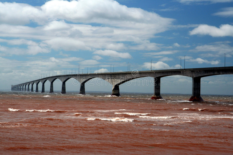 Confederation Bridge in Canada. Sea below is red after storm churned up clay stock images