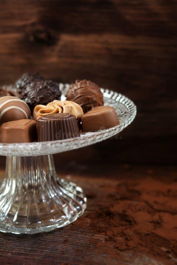 Confeitos finos do chocolate em um étagère de vidro elegante contra a imagem de stock royalty free