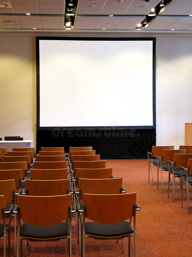 Conference 6. Portrait photo of blank conference room projector screen from audience