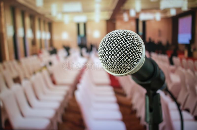 Microphones on abstract blurred of speech in seminar room or front speaking conference hall light, white chairs for people in eve royalty free stock images