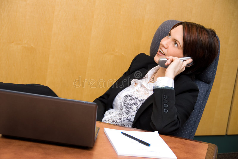 Conference call. Cute business woman on the phone chatting royalty free stock image