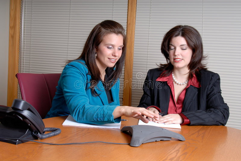 Conference Call Meeting. Two Young Businesswoman Taking Part In A Conference Call In An Office Boardroom royalty free stock photo