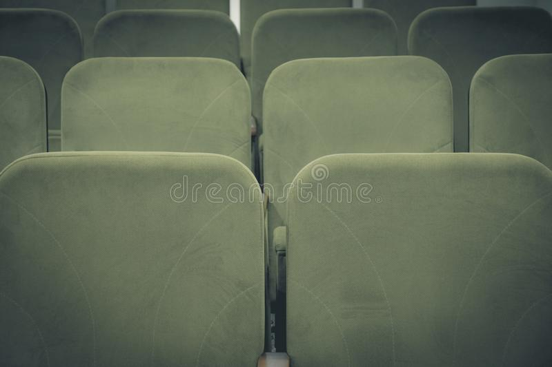 Conference hall or cinema interior with rows of green chairs royalty free stock photo