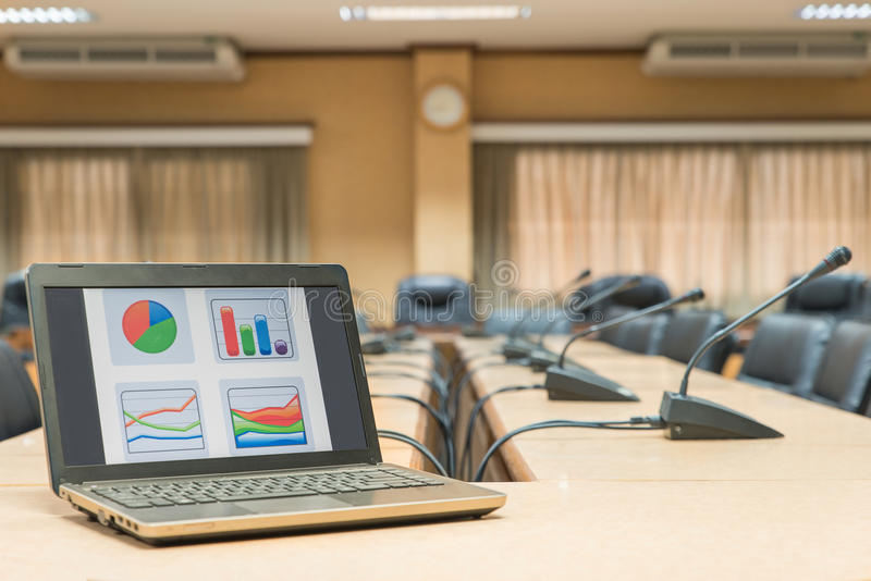 Before a conference,Laptop in front of empty chairs at conference room royalty free stock photography