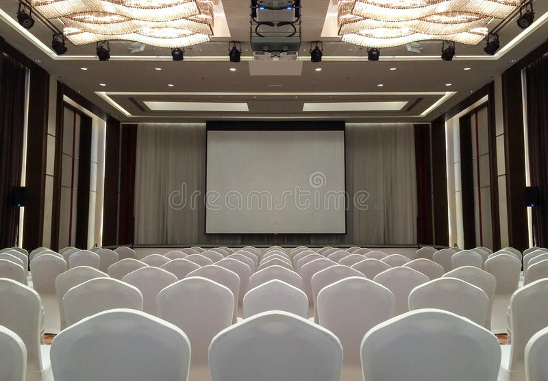 Conference Meeting Room with ceiling LED lights, Row of White Chairs, with Stage and Empty Screen for Business Meeting, Conference stock images