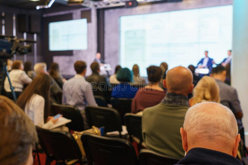 Conference participants, events, presentations, listen to the speaker sitting in chairs. stock photography