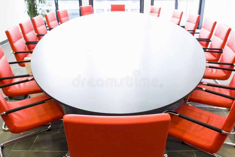 Conference room with red chairs. Meeting room with red chairs and oval conference table, Focus on the chair in the foreground royalty free stock photography