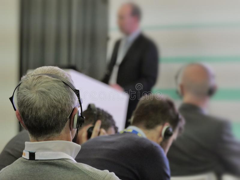 Conference to business people wearing headphones selective focus on foreground royalty free stock photo