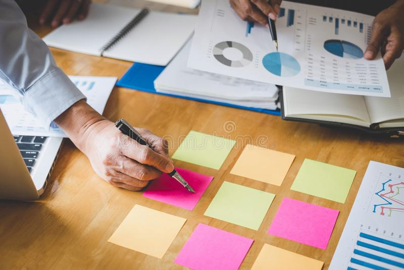 Conferencia de funcionamiento del Co, colegas del equipo del negocio que discuten trabajando an?lisis con datos financieros y com imagenes de archivo