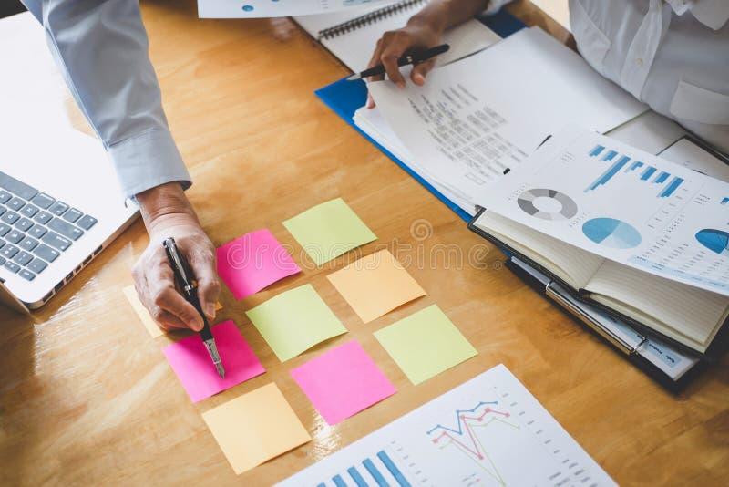 Conferencia de funcionamiento del Co, colegas del equipo del negocio que discuten trabajando an?lisis con datos financieros y com imagen de archivo libre de regalías