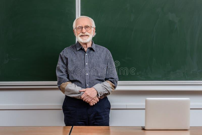 conferenciante mayor sonriente que se coloca en sala de clase y la mirada imagen de archivo libre de regalías