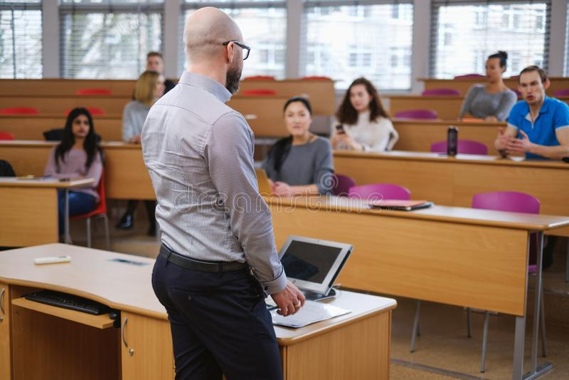 Conferenciante y grupo multinacional de estudiantes en un auditorio fotografía de archivo