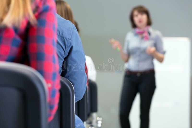 Conferente fêmea que entrega a apresentação à audiência imagem de stock