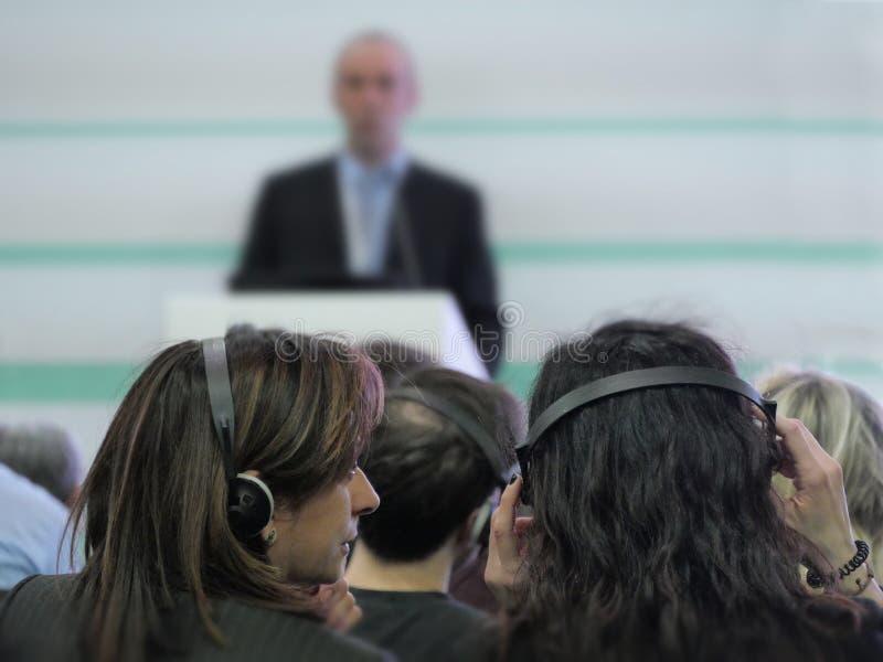 Conferentie aan bedrijfsmensen die hoofdtelefoons selectieve nadruk op voorgrond dragen royalty-vrije stock afbeeldingen