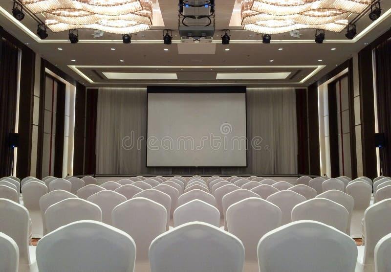 Conferentievergaderzaal met plafond LEIDENE lichten, Rij van Witte Stoelen, met Stadium en het Lege Scherm voor Commerciële Verga stock afbeeldingen