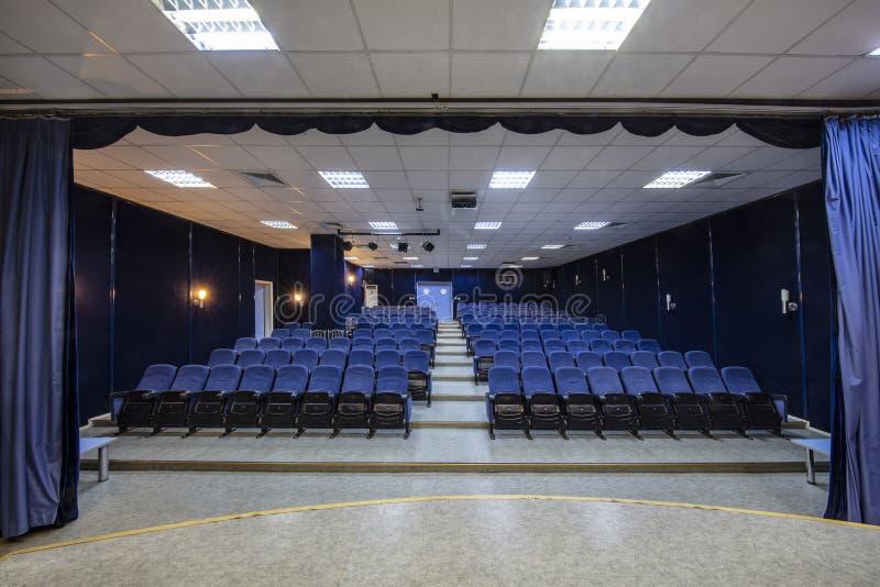 Conferenza, teatro o corridoio vuoto del cinema con le file dei sedili blu immagine stock