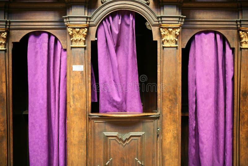 Confesonario con las cortinas púrpuras fotos de archivo