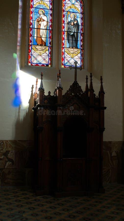 Confessionnal au-dessous d'une fenêtre en verre teinté dans une église images libres de droits
