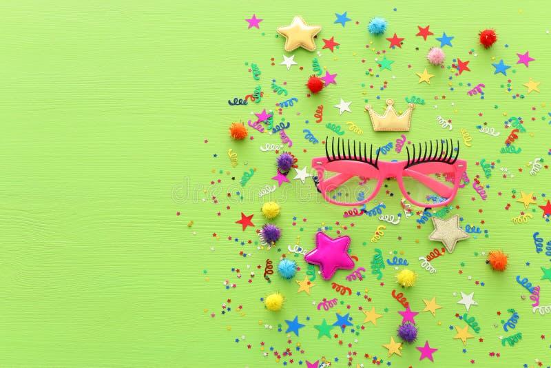 Confetes coloridos do partido e vidros cor-de-rosa engraçados sobre o fundo de madeira verde Vista superior, configuração lisa foto de stock royalty free
