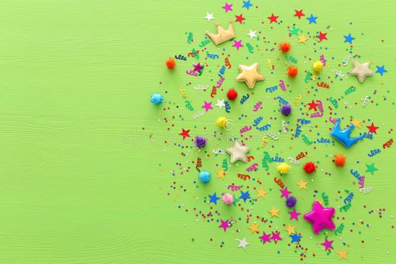 Confetes coloridos do partido sobre o fundo de madeira verde Vista superior, configuração lisa fotografia de stock royalty free
