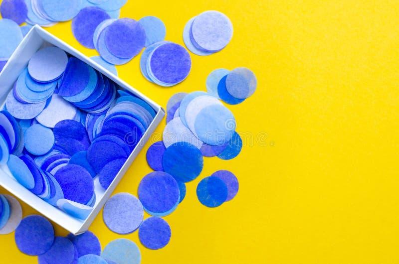 Confetes redondos em uma caixa quadrada em um fundo alaranjado imagem de stock royalty free