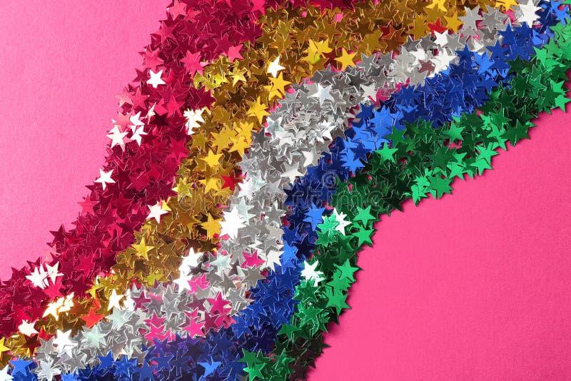 Confeti brillante en la forma de estrellas en fondo rosado imagen de archivo