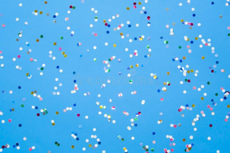 Confeti coloreado dispersado en el papel en colores pastel azul fotografía de archivo