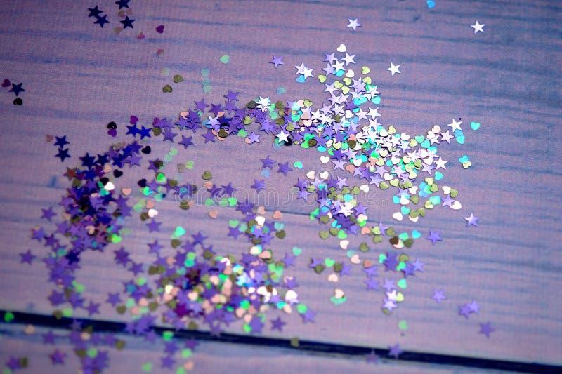 Confeti colorido en la forma de un corazón delante del fondo púrpura foto de archivo libre de regalías