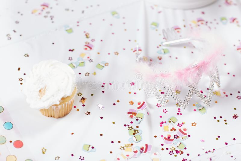 Confeti dispersado y magdalena helada en la tabla imagenes de archivo