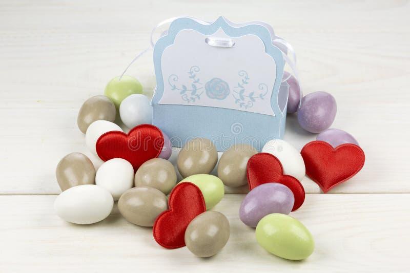 Confeti en forma de corazón rojo azucarado coloreado de las almendras y caja parecida al papel fotografía de archivo