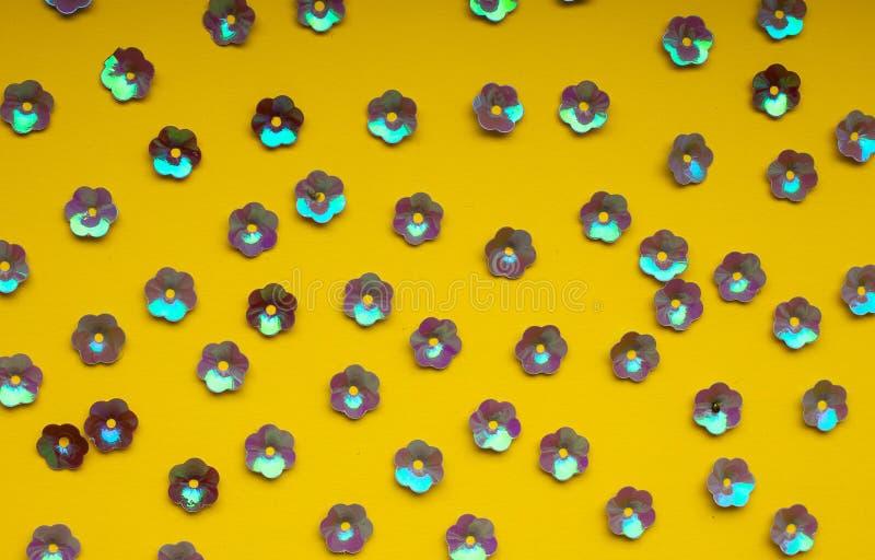 Confeti púrpura floral en el fondo amarillo, visión superior, modelo inconsútil foto de archivo