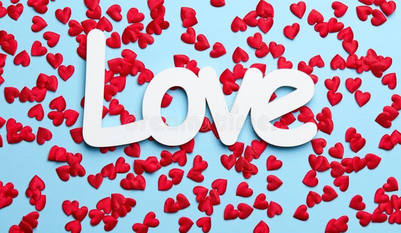 Confeti rojo en fondo azul con amor imágenes de archivo libres de regalías