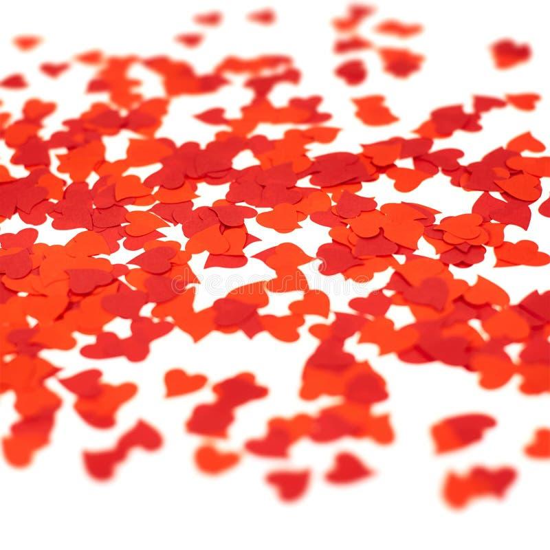 Confeti rojo en forma de corazón dispersado imagenes de archivo