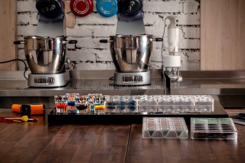 Confetteria e strumenti di cottura per i dolci sulla tavola di legno Muffe di plastica, miscelatori, coloranti alimentari, tazze  fotografie stock libere da diritti