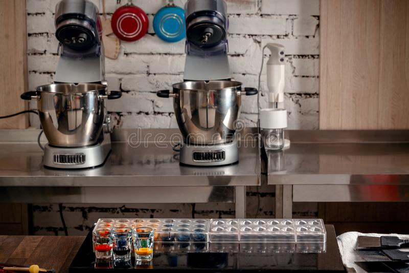 Confetteria e strumenti di cottura per i dolci sulla tavola di legno Muffe di plastica, miscelatori, coloranti alimentari, tazze  fotografia stock libera da diritti