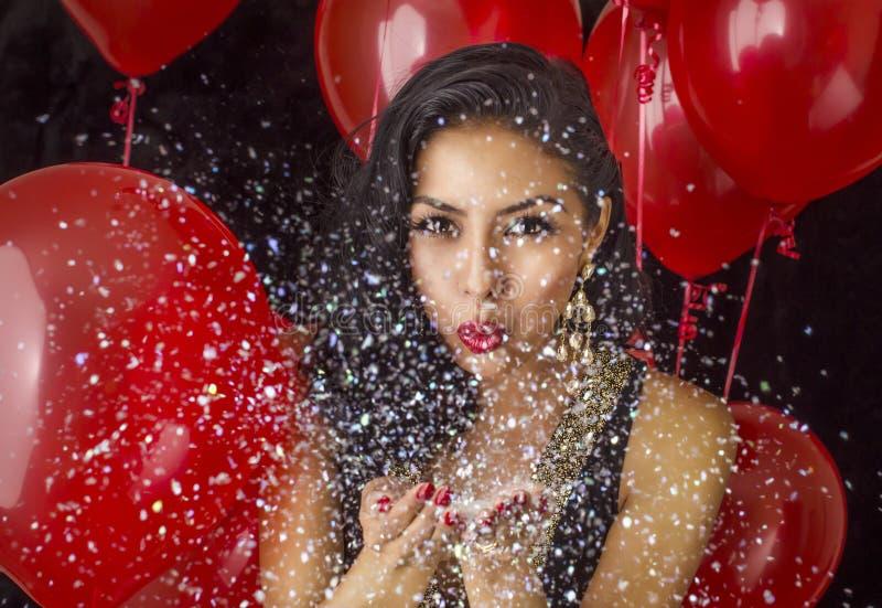 Confetti красивой молодой женщины дуя стоковые изображения