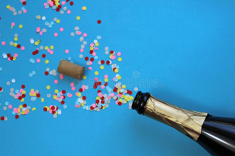 Multi-colored confetti flew out of the bottle royalty free stock photo
