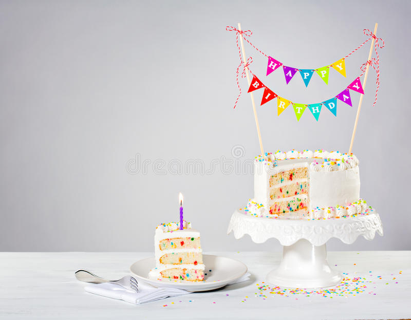 Confetti Birthday Cake. Confetti Buttercream birthday cake with colorful bunting and sprinkles over white background royalty free stock images