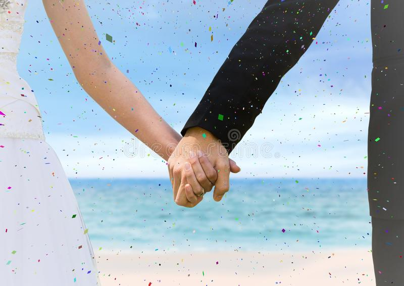 Confetti and bride and groom holding hands at blurry beach royalty free stock photos