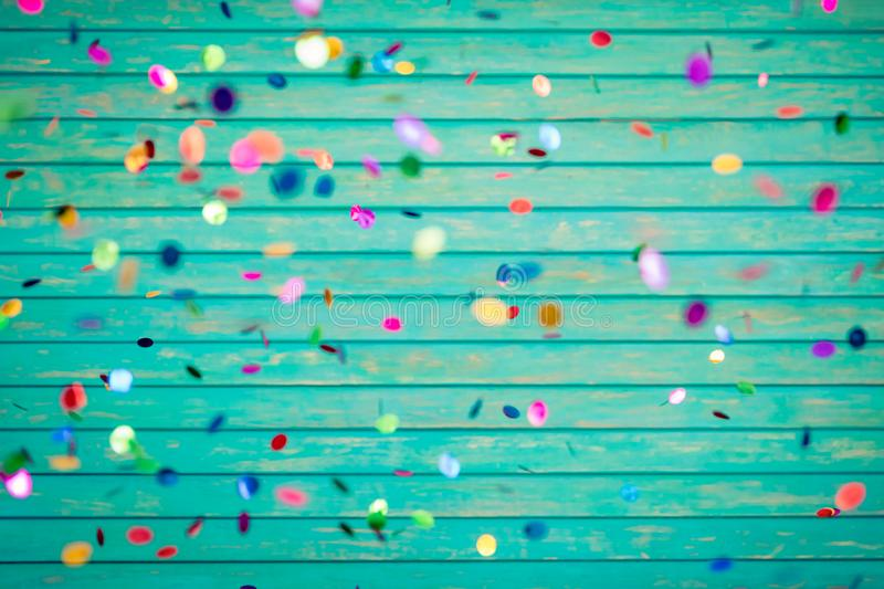 Confetti falling on wooden background stock photo