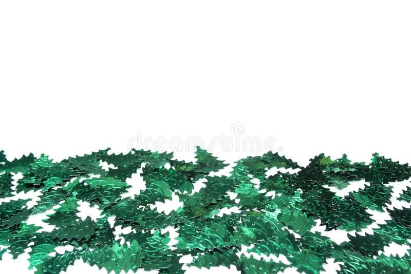 Confetti. New Year. Christmas trees confetti. Foiled frame. Decor. Confetti New Year. Christmas trees confetti. Foiled frame. Decor. Green sequins stock photo