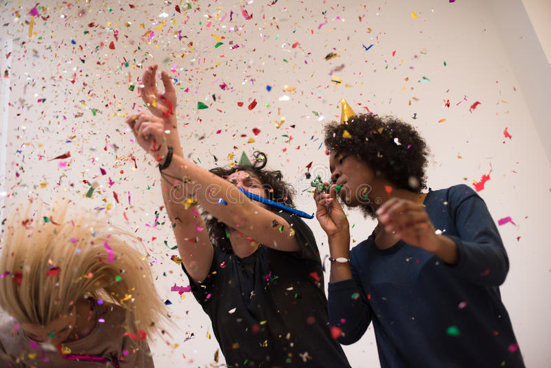 Confetti party. Happy young people group celebrating new year eve while dancing and have fun at home stock photo