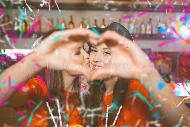 Confetti przyjęcie Dwa młodej lesbian dziewczyny całują serce z ich rękami i robią przy tłuc przyjęcia obraz stock