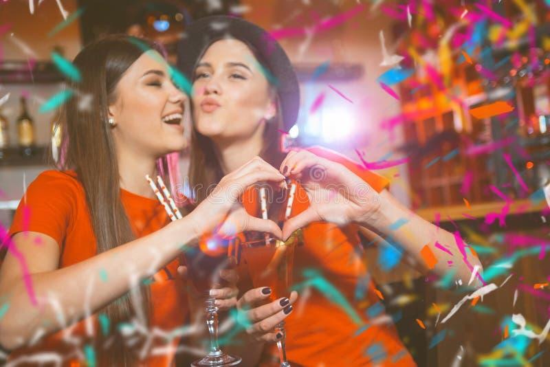 Confetti przyjęcie Dwa młodej lesbian dziewczyny robią sercu z ich rękami przy tłuc przyjęcia obraz stock