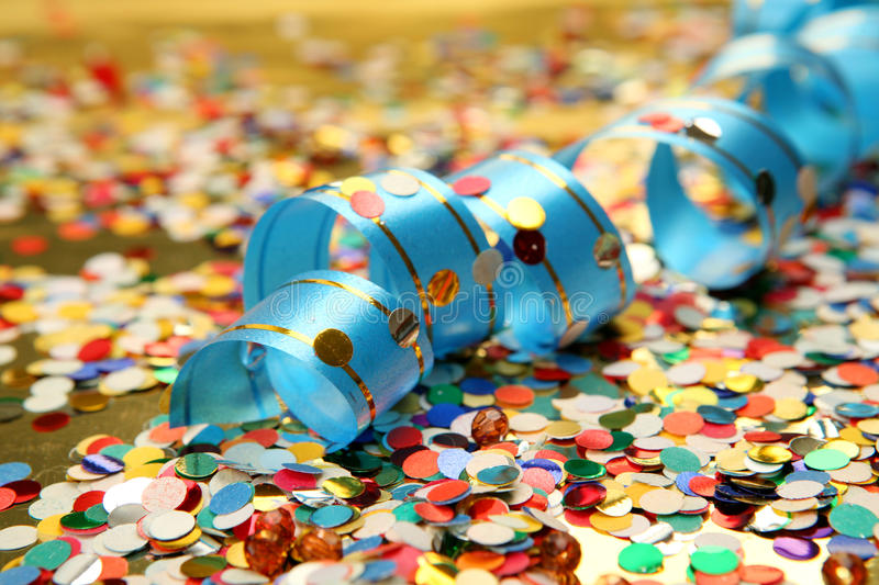 Confetti and streamer. Streamer and color confetti on a gold background royalty free stock image