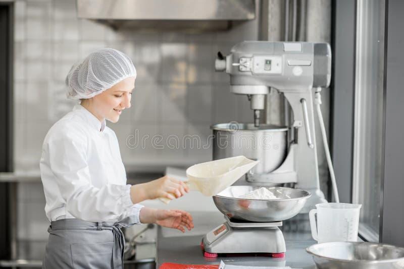 Confettiere della donna che lavora alla fabbricazione del forno fotografia stock