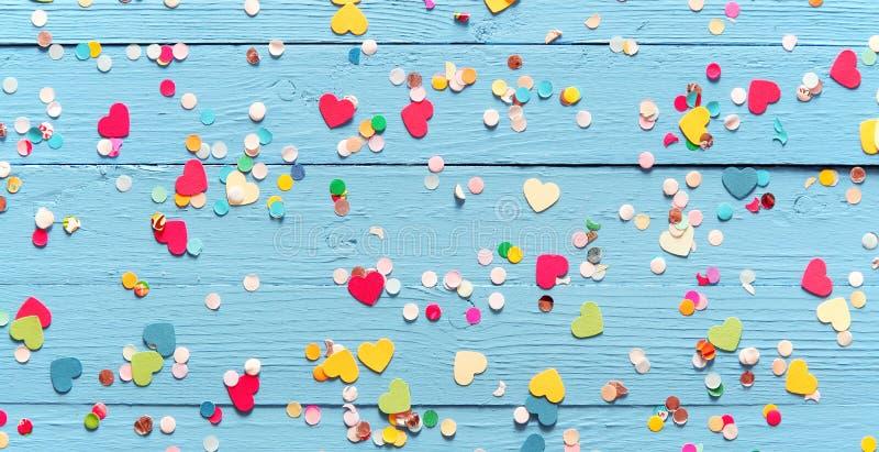 Confettis colorés de partie sur le bois bleu photographie stock libre de droits
