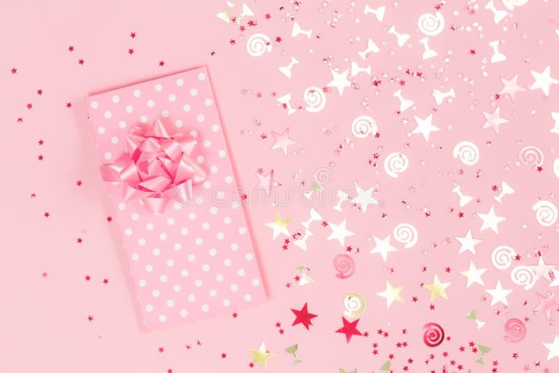 Confettis de f?te assortis de scintillement d'or sur le rose photographie stock